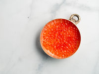 Bowl of red caviar on white marble