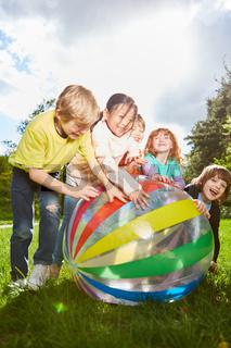 Fröhliche Kinder spielen mit einem bunten Ball