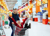 Young handsome guy rides a girl in a supermarket in a trolley