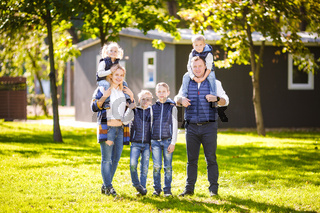 Theme family active leisure outside in nature. large Caucasian family with four children. Mom and Dad actively relaxing. enjoy life in park near house on grass. Children on back shoulders roll on top