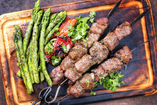 Traditional Russian shashlik on a barbecue skewer with green asparagus and paprika as top view on a burnt cutting board