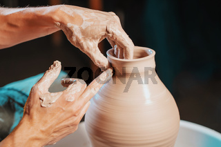 Unknown craftsman creates jug. Focus on hands only. Small business, talent, inspiration concept. Overhead view. Working process of man's work at potters wheel in art studio