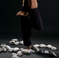 Man staying in yoga pose with white stones near by