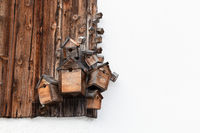 Several wooden bird boxes on a wooden wall