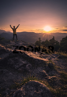 Happy man with open raised arms on the Top of a Mountain during the Sunset