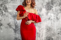 Smiling woman in red dress with a glass of champagne. Party concept