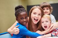 Lachende Erzieherin wird von Kindern umarmt