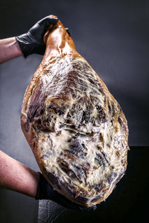 Traditional Spanish jamon Iberico dry aged haunch of a duroc pork as closeup in hands presented on black background