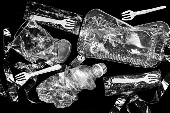 Various disposable crumpled plastic garbage isolated on a black background. Concept of recycling plastic and ecology.