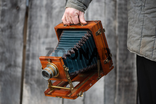 Photographer holds old large format studio camera, 5x7 inches. Concept - photography of the 1930s-1950s