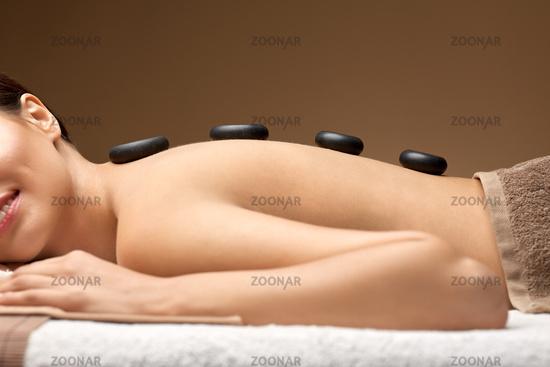 smiling woman having hot stone massage at spa