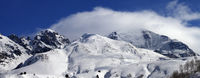 Off-piste ski slope and snowy mountains in clouds