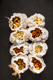 Assortment of fresh nuts in textile bags, vegetarian snack