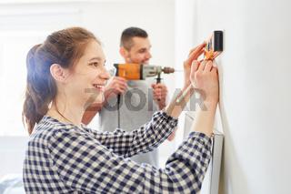 Frau und Freund beim Renovieren mit Wasserwaage