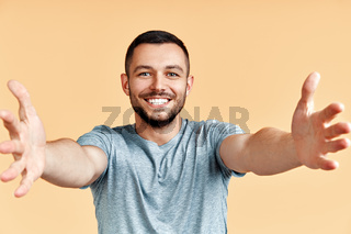 Handsome happy man with open hand ready for hugs on yellow background