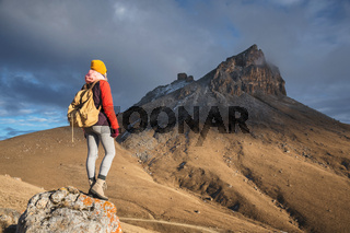 Portrait from the back of a girl traveler in a jacket with a cap and a backpack stands on the background of an epic landscape with rocks