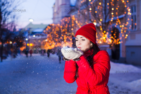 Young girl blowing away snow from mittens
