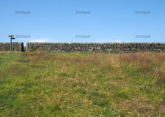 a gate in a long stone wall with a wooden signpost pointing out directions in a green field with blue summer sky