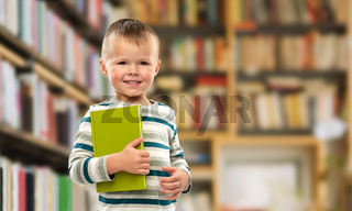 portrait of smiling boy holding book over library