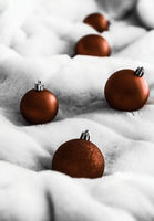 Chocolate brown Christmas baubles on white fluffy fur backdrop, luxury winter holiday design background