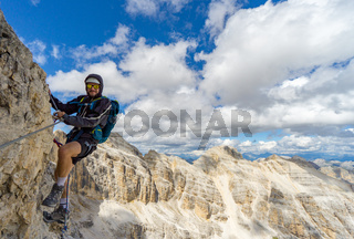 young male mountain climber on a steep and exposed rock face climbing a Via Ferrata