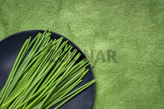 green chives on black plate