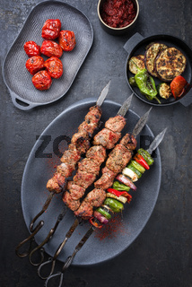Traditional Russian shashlik on a barbecue skewer with vegetable and sumach paste as top view on a modern design plate