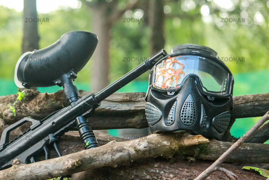 Paintball mask set and gun. Paintball mask hit in glasses after play. A paintball gun and a mask placed on the woods in the woods. Natural background.