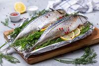 Raw mackerel on fresh dill with lemon slices.