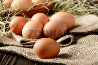 Fresh brown organic chicken eggs on wooden table and hemp burlap