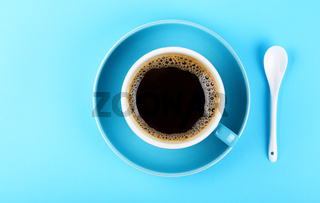 Full cup of black coffee and saucer over blue