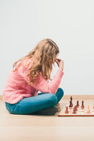 Girl deeply thinking about next move during chess game