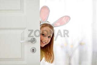 happy girl with easter bunny ears peeking out door
