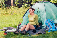 Spending a vacation on camping. Woman resting next to tent