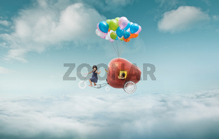 Happy sister enjoy with fantasy apple cycle ride  and floating in sky with bunch of colorful balloons .