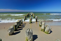 Old wooden breakwater on sandy shore of Baltic sea