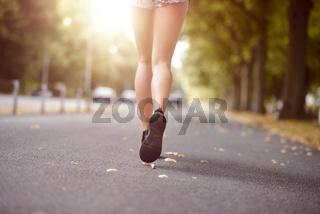 Junge schlanke Frau läuft im Sommer auf einer Straße
