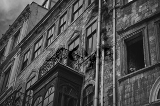 Istanbul, Turkey - April 8, 2012: Turkish man smoking peeping shyly to the window of his house in Istanbul, black and white photo.