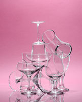 Composition of glass glasses of different shapes on a rose background. Art photo in pastel colors.