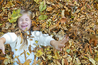 Kid plays in autumn park. Child throwing yellow and red leaves. Little girl with oak and maple leaf. Fall foliage