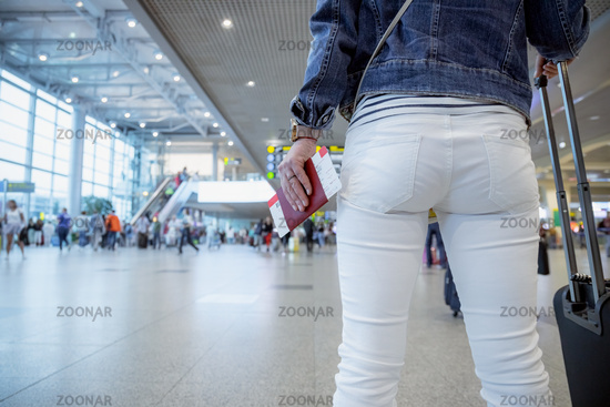 Female Traveller holds a passport and a ticket against the background of the airport hall