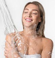 Pretty girl enjoying water stream studio shot