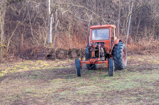 Tractor. Old rusty red antique tractor from a farm in the woods.