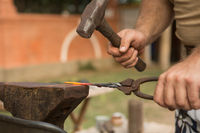 Blacksmith working on metal on an anvil in the forge