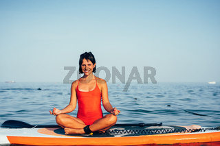 Young woman doing yoga on sup board with paddle