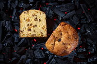 Panettone placed on black charcoal with red fire background