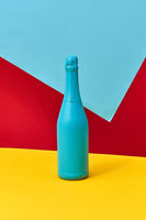Decorative painted blue champagne bottle on a tricolor background.