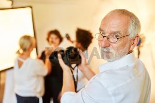 Erfahrener Porträtfotograf mit Kamera und Team