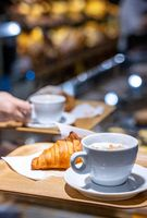 Coffee and croissant served in a pastry shop blurred background