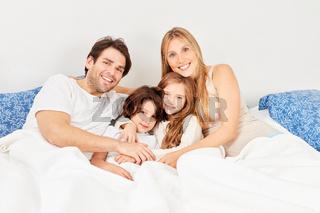 Glückliche Familie mit zwei Kindern im Bett